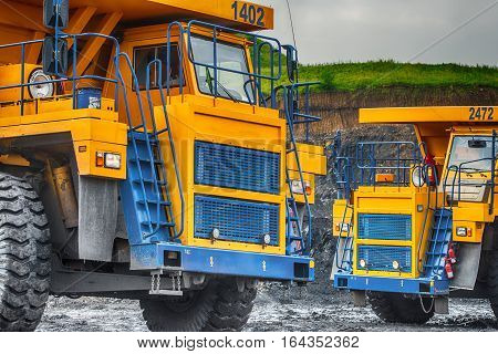 NOVOKUZNETSK, RUSSIA - JULY 26, 2016: Big yellow mining trucks at worksite