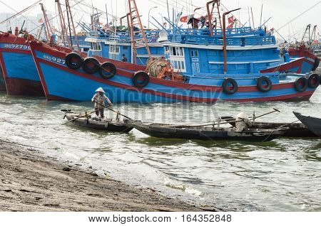 Vietnamese woman paddling alongside large fishing boats at the fishing village in Da Nang. December 26 2013 - Da Nang South Vietnam