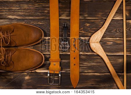 Brown men's boots, brown leather belt and hanger on wooden background. Casual stile set