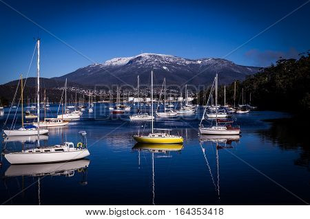 Boats and reflections in Lindisfarne, Hobart, Tasmania, Australia in winter with view on Mount Wellington covered in snow