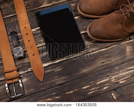 Men's brown clothing and accessories set: boots, leather belt, watch and pc-tablet