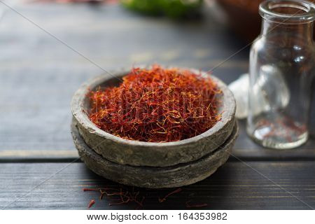 Raw Organic Red Saffron Spice in a clay bowl on wooden table