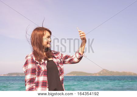 Blonde woman taking selfie using smartphone at sea travel lifestyle and modern technology concept.