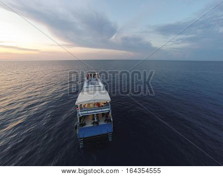 Amazing view to cruise boat sailing in open sea at windy day. Aerial photo drone view - birds eye angle. Cruise boat theme.