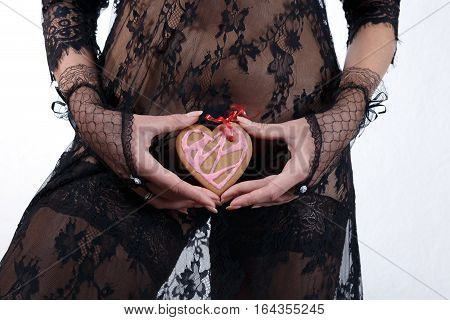 Female hands in black lace gloves hold heart shaped gingerbread cookie with red ribbon against black transparent lace dress incognito close up. Valentine's day and love concept