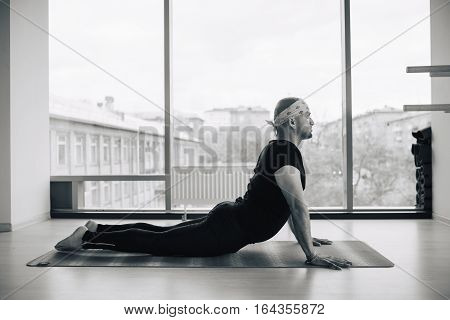 Side view of indian man doing the cobra pose in a bright fitness studio.