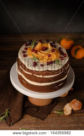 The chocolate cake with clementines, cranberry and rosemary on cakestand wooden background. Still life.