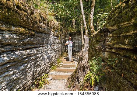 The tourist in the rocky maze that occurred 20 million years ago by tectonic faults on the territory of the yew & boxwood grove in Khosta district in Sochi. Russia, Krasnodar Krai