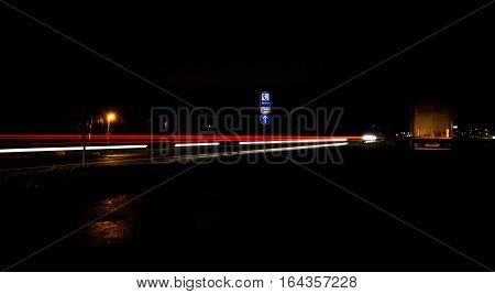 Autos fahren bei Nacht an einer Strasse an einem Notruf-Schild vorbei