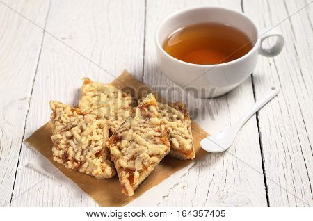 Cup of tea and homemade shortbread cookies with jam for breakfast on white wooden table