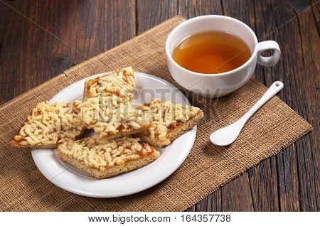 Homemade shortbread cookies with jam and cup of tea on dark wooden table