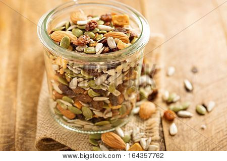 Dried fruit and nuts trail mix with almonds, raisins, seeds and apples in a glass jar