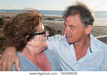 Senior Couple In Love By The Sea And Ocean On A Bench