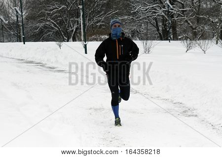 BUCHAREST ROMANIA - January 07 2017: A sportsman runs on snow in the central park in a winter day during the vacation.