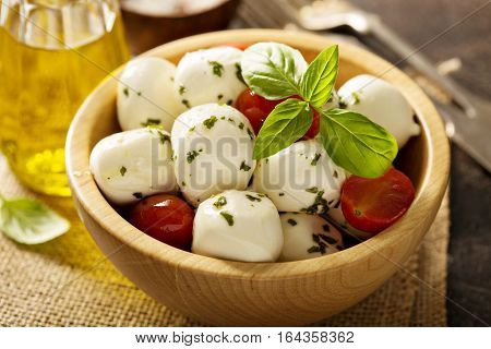 Fresh mozzarella marinated with herbs and served with cherry tomatoes and fresh berries, Caprese salad
