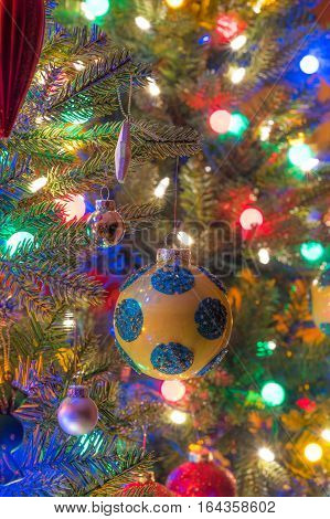 Christmas tree decorations.  Yellow, shiny finish, orb with blue circles, glows, surrounded by bright and vibrant multicoloured mini-lights.