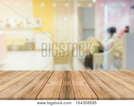 Wooden board empty table in front of blurred background. Perspective brown wood table over blur room in hospital background - can be used mock up for display or montage your products.