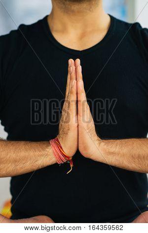 Hands in Namaste prayer mudra by Indian man practicing yoga.