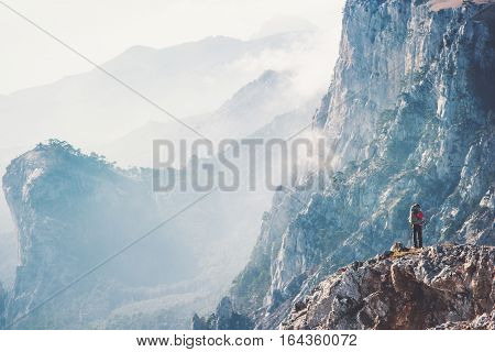 Traveler on cliff hiking with backpack Travel Lifestyle concept adventure active vacations outdoor rocky mountains Landscape aerial view on background