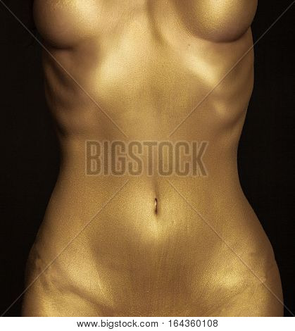 Golden female body of young sexy beautiful woman with bare chest and belly on black background. Metallic art, body art. Slim, fit woman. Gold skin.