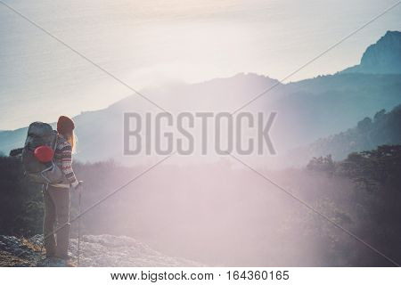 Woman Traveler with backpack hiking on cliff Travel Lifestyle concept adventure active vacations outdoor sunset aerial view from mountain summit on background
