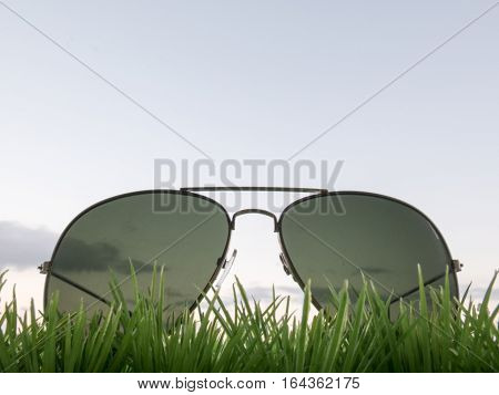 Sunglasses in the grass on blue sky background