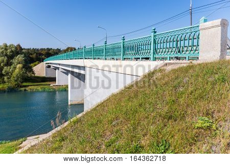 White concrete bridge with forged green fencing