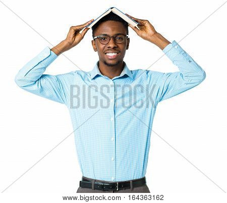 Happy african american college student standing with book on his head on white background
