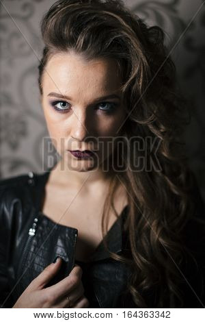 Punk rock style or halloween make-up. Fashion woman model face with bright glamour makeup. Perfect skin, black gloss eyeshadows on eyes and dark brown glossy lips visage. Portrait close-up.