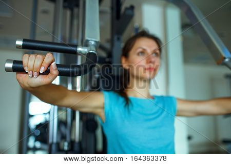 Athletic woman works out on training apparatus in fitness center
