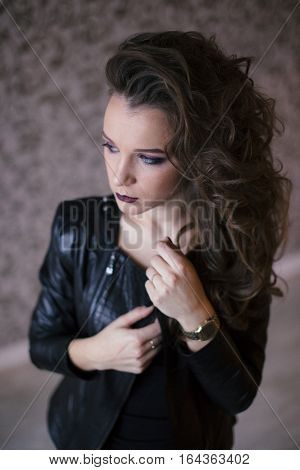 Punk rock style or halloween make-up. Fashion woman model face with bright glamour makeup. Perfect skin, black gloss eyeshadows on eyes and dark brown glossy lips visage.
