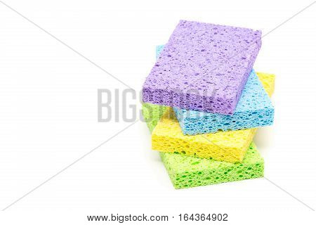 Stack of unused clean green yellow blue and violet cleaning sponges over white background