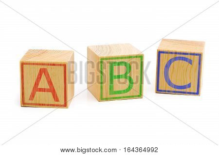 Letters A B C imprinted on three brown wooden cubes lined up in a row over white background