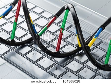 DNA molecule model on computer keyboard. Artificial intelligence concept