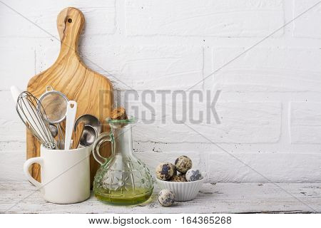 Kitchen Still Life. Olive oil in a jug, quail eggs and kitchen tools for baking, olive cutting board on a wooden shelf in the background of a white brick kitchen wall. selective focus