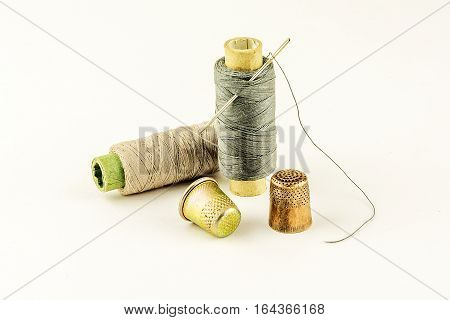 Two thimble for sewing and two spools of thread on a light background