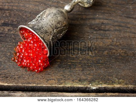 Red  caviar beads on silver cup close-up isolated on wood background