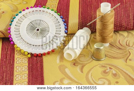 At curtain fabrics are two reels of thread for sewing with needle and thimble