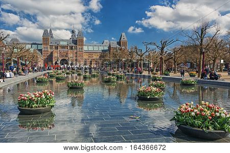 Amsterdam, Netherlands, April 10, 2016: planters filled with tulips in the pond during the Tulip Festival in Amsterdam with in the background The Rijksmuseum