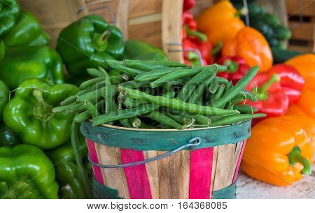 green beans in wooden bushel basket with colorful peppers at the farmers market