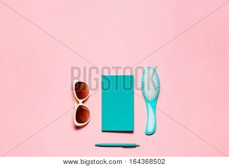 Flat feminine accessory composition of hairbrush, glasses, diary and pen isolated on pink copy space.