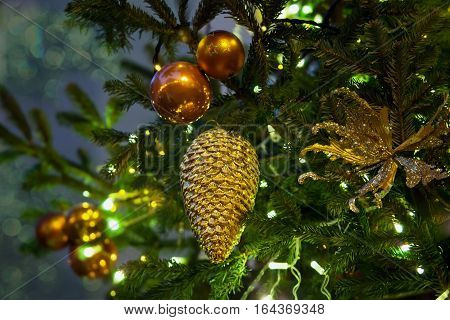 Fir branch with cone and balls and festive lights on the Christmas background with sparkles.