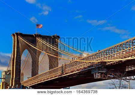 American flag on Brooklyn Bridge Brooklyn bridge with cloudy blue sky New York