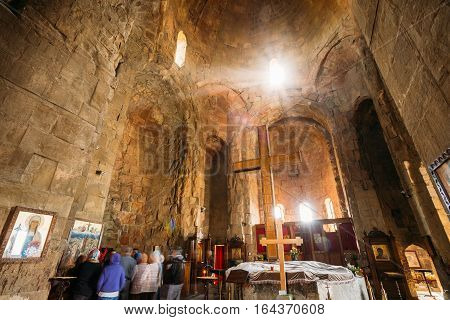 Mtskheta, Georgia - May 20, 2016: Back View Of Group Pilgrims Standing Near The Icon On Stone Wall In Jvari Church. The Interior Of Ancient Georgian Orthodox Monastery, Famous Landmark.