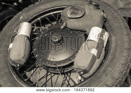 Gas mask and water containers over tire. Image with gas mask and two water containers in black and white placed over wheel.