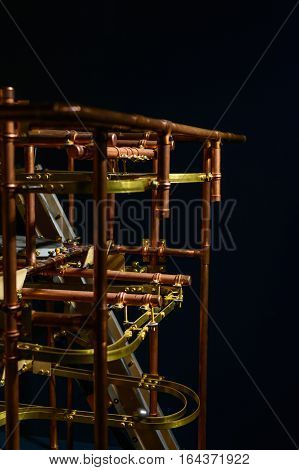 Vertical view with metallic mechanism. Metallic ball rolling down the slides over technical system.