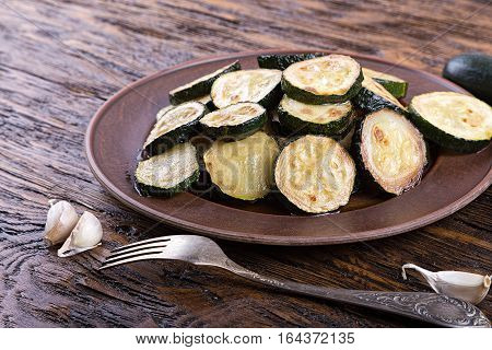Fried zucchini in a clay plate on a wooden table. burlap on the table two raw zucchini and garlic.