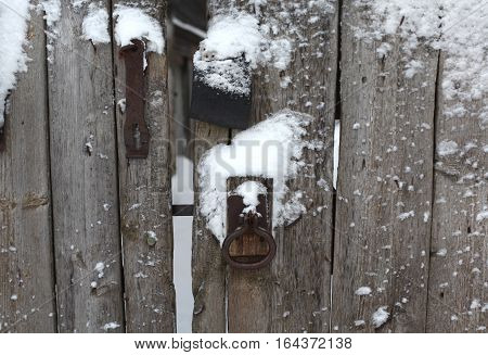 unpainted old wooden fence with rusty iron door with lock and handle in the form of an old ring. View winter in the snow