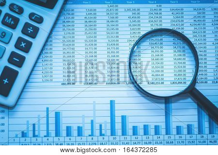 Financial fraud investigation, audit and analysis concept. Spreadsheet bank accounts accounting with calculator and magnifying glass.