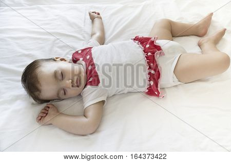 Calm sleeping baby at midday in the bed